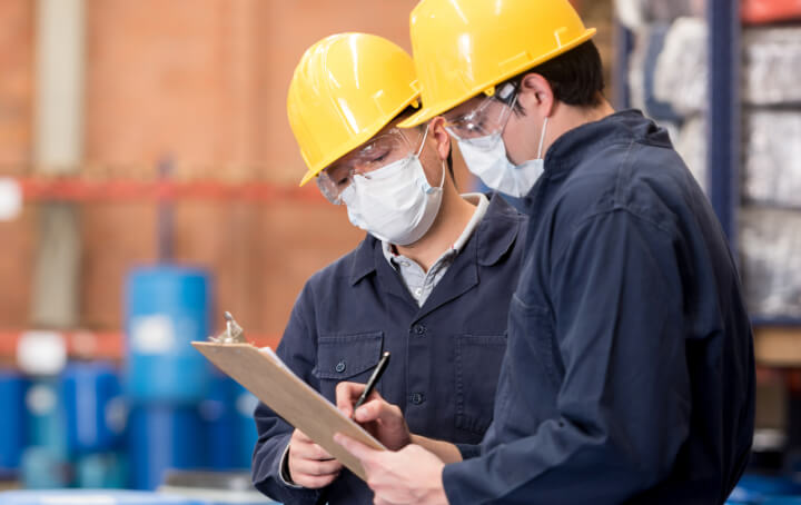Two workers in masks and yellow hard hats conversing in an industrial setting.
