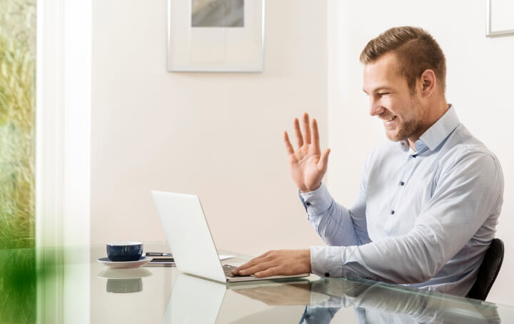 A man smiling and waving at his laptop screen.